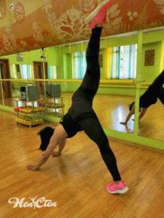 Фото девушки выполняющей растяжку мышц антагонистов в собаке мордой вниз с поднятой вверх ногой