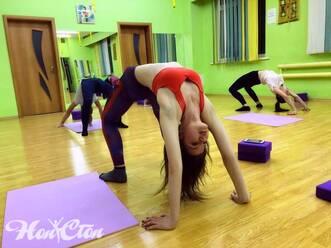Девушка в ярком топе занимается растяжкой в уютном фитнес зале Нон-стоп в Витебске