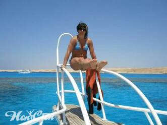 Фитнес тренер Ирина Андронова на отдыхе в Египте на яхте в голубом купальнике выполняет силовой элемент уголок на фоне сине-голубого моря