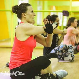 Елена Федотова в розовой майке показывает упражнение на растяжку мышц рук в клубе Нон-стоп, Витебск