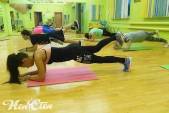 Девушка выполняет упражнение планка на одной ноге на силовом тренинге Сергея Рачицкого - тренера клуба Нон-стоп в Витебске