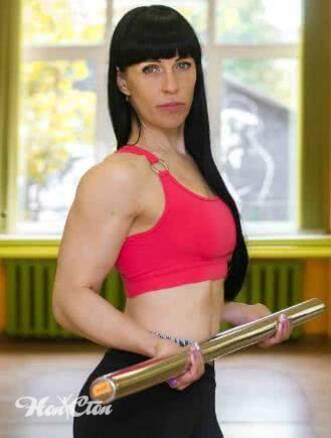 Ирина Андронова тренер по фитнес программе силуэт в зале на московском в красном топе выполняет упражнение для бицепса рук с бодибаром