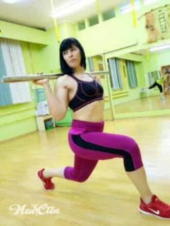 Ирина Андронова тренер по фитнесу выполняет упражнение выпады с бодибаром в черном топе и малиновых легинсах