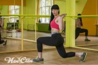 ирина Андронова делает выпады на левую ногу с бодибаром в черных легинсах и розовом топе в зале в зеркальном зале
