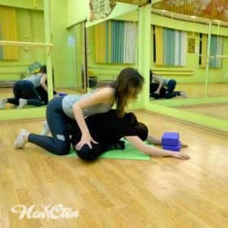 Фото девушки и инструктора выполняющих упражнение бабочка для поперечного шпагата