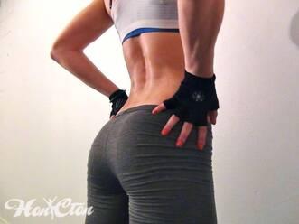 Тренер по фитнесу Ирина Андронова в серых легинсах и белом топе показывает красивую накаченную спину и круглые накаченные ягодицы