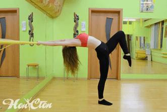 Тренер Курякова Анастасия в ярком топе растягивает спину около гимнастического станка в фитнес клубе Нон-стоп в Витебске