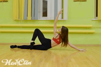 Тренер по стретчингу в ярком топе выполняет элемент растяжки на полу в клубе Нон-стоп, Витебск
