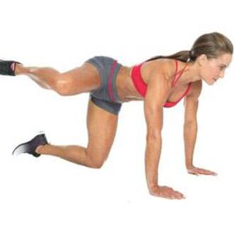 Красивая девушка в шортах и топе выполняет отведение ноги в сторону  на силовой тренировке для девушек