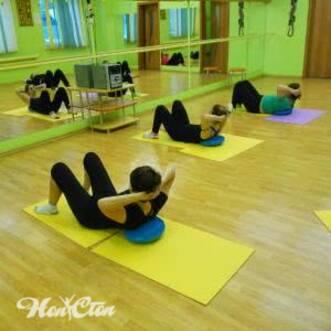 Фото группы по пилатесу выполняющей упражнение на пресс