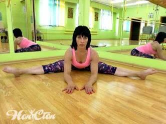 Фото девушки-инструктора выполняющих упражнение широкая складка для поперечного шпагата