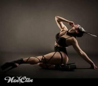 Ирина Андронова тренер по стрип пластике в сексуальном черном костюме и кожаной маске сидит в сексуальной позе