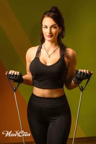 Ольга Семова в черном топе демонстрирует упражнение для рук в витебском фитнес клубе Нон-стоп