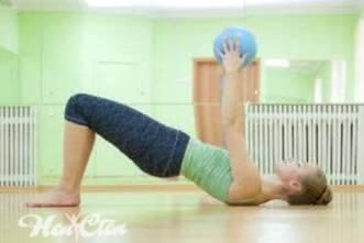 На тренировке для женщин для спины девушка выполняет упражнение с мячом