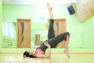 Девушка на тренировке для женщин выполняет упражнение полумост