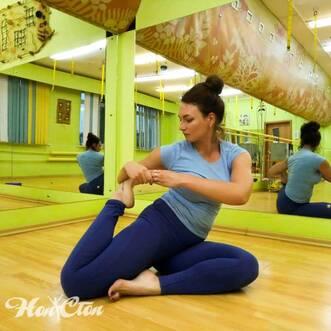 Ольга Семова в голубом топе выполняет элемент из йоги в фитнес клубе Нон-стоп