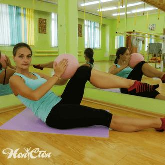 Тренер по пилатесу Анастасия Маркова демонстрирует упражнение с мячом на мышцы пресса в клубе Нон-стоп, Витебск