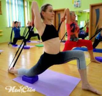 Фото инструктора выполняющего растяжку мышц рук и ног с помощью ремня.