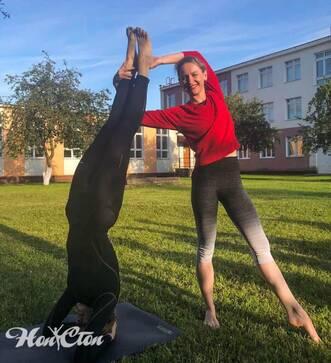 Тренер по пилатесу фитнес клуба Нон-стоп Бондарева Надежда помогает своему клиенту выполнять стойку на голове