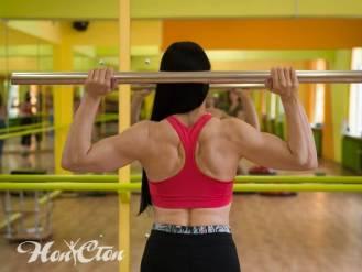 Тренер по фитнесу Ирина Андронова в красном коротком топе и черных легинсах выполняет упражнение с бодибаром для спины