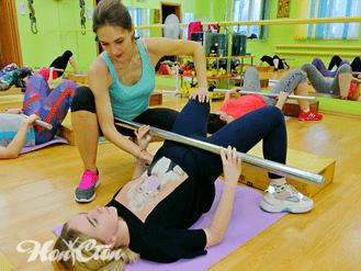 """Маркова Анастасия - тренер по аэробике """"Идеал"""" помогает девушке выполнять упражнение в витебском фитнес клубе Нон-стоп"""