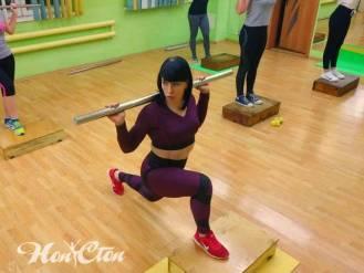 Ирина Андронова тренер по фитнесу в бордовых легинсах и бордовом топе выполняет выпады на степе с бодибаром