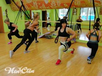 Спортивные девушки выполняют упражнения на руки в пелях TRX