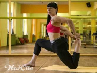 Тренер по растяжке Ирина Андронова в розовом топе и черных коротких легинсах делает тянет переднюю поверхность бедра