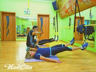 Тренер витебского фитнес клуба Нон-стоп помогает выполнять упражнения на петлях TRX